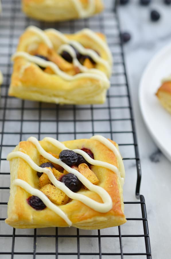 Peach Blueberry Tart- This easy fruit tart is the perfect use of summer's juicy blueberries and peaches. The tart is made out of Puff Pastry and then topped with seasoned blueberries and peaches with a vanilla cream cheese drizzle. www.domesticdee.com